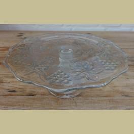 Kleine glazen taartschaal op voet met druiven en wijnbladeren